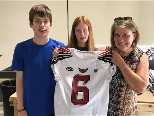 Julie Stratman, mother of Matt Stratman, holds up the freshman jersey the Lakota West Firebirds will be wearing this fall thanks to the family.  From left is Tom, Eva and Julie Stratman.