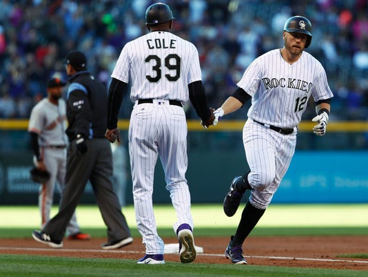 Colorado Rockies third base coach Stu Cole, left, congratulates Mark Reynolds as he circles the bases after hitting a two-run home run off San Francisco Giants starting pitcher Matt Moore in the first inning of a baseball game Saturday, April 22, 2017, in Denver. (AP Photo/David Zalubowski)