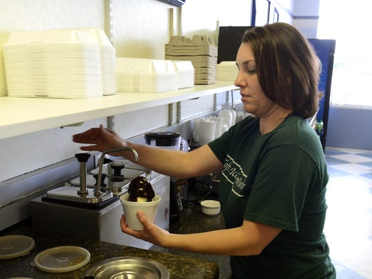 Amber Keiser prepares a sundae for a customer at Tofts in Fremont on Tuesday, Sept 30, 2014.