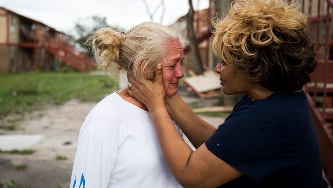 """Genice Gipson comforts her lifelong friend, Loretta Capistran, outside of Capistran's apartment complex in Refugio, Texas, on Monday, Aug. 28, 2017. """"We got to be strong, baby,"""" Gipson told Capistran. Hurricane Harvey made landfall in Rockport, Texas, 20 miles south of Refugio."""
