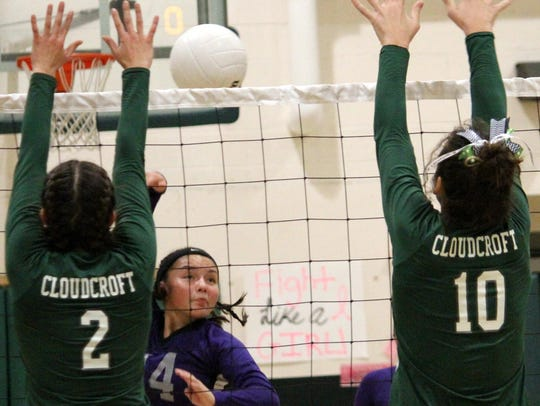 Mescalero's Alyn Kazhe-Kirgan, center, spikes a ball