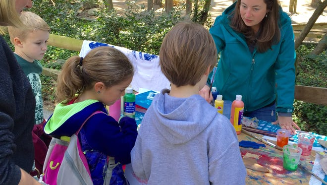 This April 16, 2016 photo shows, from left, parent Julie Brown with her son, Mason, and friends Lynleigh Willing and Nathan Riggin at a fish-printing-on-paper exhibit sponsored by the Nanticoke Watershed Alliance. On the opposite side of the table is an Alliance exhibitor who helped children with their craft. The exhibit was part of an Earth Day event at the Salisbury Zoo.