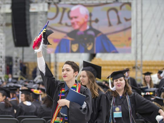 Notre Dame graduates walk out of Notre Dame Stadium in protest as Vice President Mike Pence speaks during the 2017 commencement ceremony, Sunday, May 21, 2017, in South Bend, Ind. (Robert Franklin/South Bend Tribune via AP) ORG XMIT: INSBE703