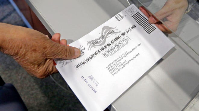A voter hands his absentee ballot to a Miami-Dade elections official in 2016.