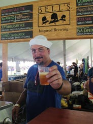 A server at the Bell's Brewery stand hands over a sample