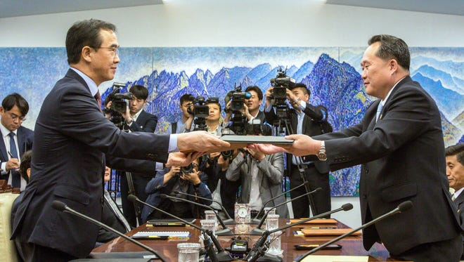 South Korean Unification Minister Cho Myoung-gyon, left, and North Korean delegation head Ri Son Gwon exchange documents signed an agreement during their meeting inside the Peace House at the southern side of Panmunjom in the Demilitarized Zone Friday, June 1, 2018.