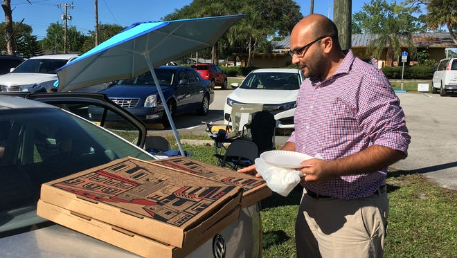 Sanjay Patel brings pizza to volunteers at McClarty Park in  Rockledge on Election Day.