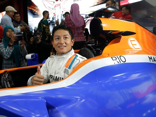 Manor F1 driver Rio Haryanto poses for photographers inside a replica of his car during a media event in Jakarta, Indonesia, Monday, March. 14, 2016. Haryanto is Indonesia's first F1 driver.(AP Photo/Achmad Ibrahim)