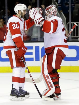 Detroit Red Wings' Drew Miller, left, celebrates with goalie Jimmy Howard after the Red Wings' 3-2 win over the San Jose Sharks on Feb. 26, 2015, in San Jose, Calif.