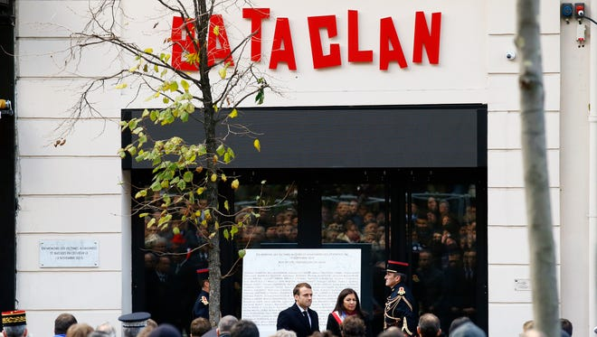 French President Emmanuel Macron, center left , flanked with Paris mayor Anne Hidalgo stand in front of the Bataclan concert hall during a ceremony marking the second anniversary of the Paris attacks, Monday Nov.13 2017.