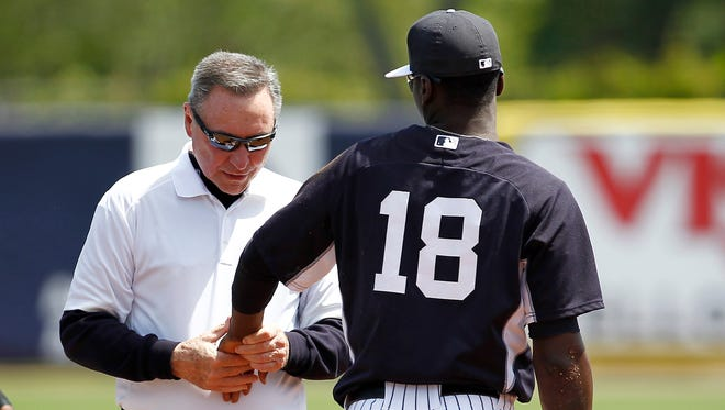 Didi Gregorius has his wrist  looked at by a trainer after diving for a ball.