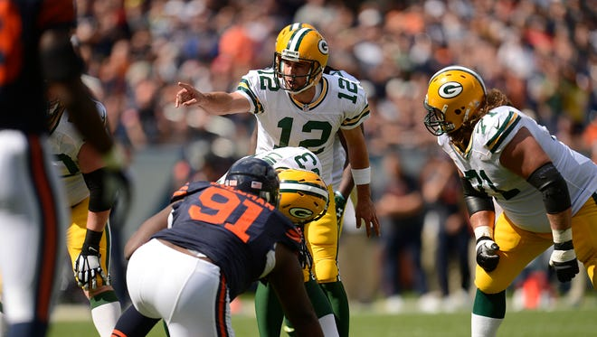 Green Bay Packers quarterback Aaron Rodgers (12) shouts instructions to his teammates at the line of scrimmage during Sunday's game against the Chicago Bears at Soldier Field.