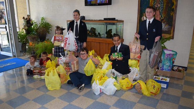 St. Mary School in East Vineland collected more than 500 cans of corn, beans and cranberry sauce plus $250 to purchase turkeys, stuffing mix, instant mashed potatoes and all the fixings for the St. Vincent DePaul Food Pantry at the Parish of All Saints in Millville. (From left) Emma and Hayden Manning, Carleigh Morton, Emma and Nicholas Battersby, Lorenzo Lopes and Harley Reed are pictured with the donations.
