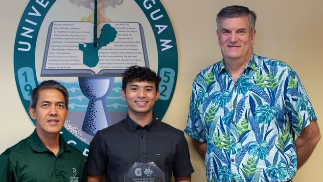 Dylan Naputi, center, receives the Student-Athlete of the Year from head coach Rod Hidalgo, left, and Randall Wiegand, University of Guam vice president for administration and finance.