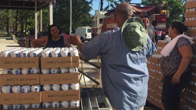 Staff from The Housing Authority of the City of Fort Myers unload cases of water at Bonair Towers.