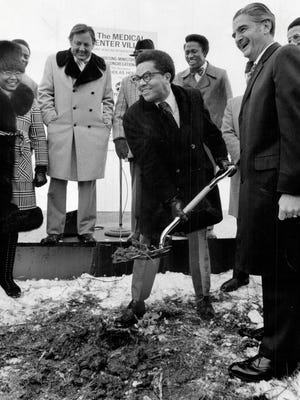 (left) David Froh, MSDHA director, and (right) John Riccardo, Chrysler Corp. president, watch as Councilman Nicholas Hood breaks ground for Medical Center Village in 1974.