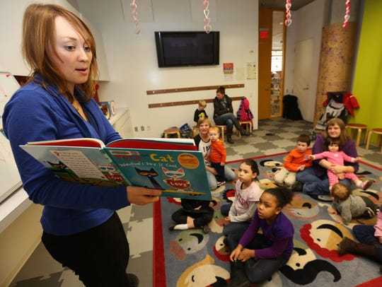 Maddie Bassman, library assistant youth services, reads a story during the Crafty Readers program at Des Moines Central Library in 2014.