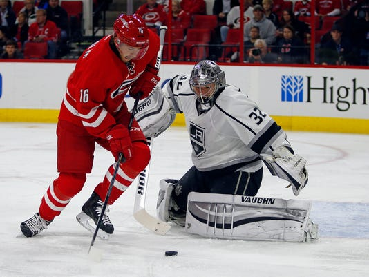 Carolina Hurricanes' Elias Lindholm (16) of Sweden, works the puck in front of Los Angeles Kings goalie Jonathan Quick (32) during the second period of an NHL hockey game in Raleigh, N.C., Sunday, Nov. 2, 2014. (AP Photo/Karl B DeBlaker)