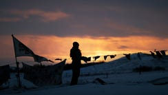 A woman watches the sunset at the Oceti Sakowin camp