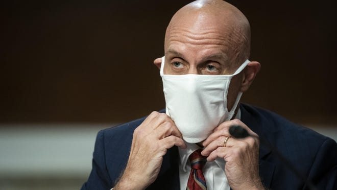Food and Drug Administration Commissioner Dr. Stephen Hahn adjusts a face covering during a Senate Health, Education, Labor and Pensions Committee hearing on Capitol Hill in Washington, Tuesday, June 30, 2020.