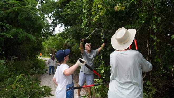 Roman Lucky, second from right, of Estero, helps remove overgrown and invasive plants along the trails at Lovers Key State Park in Bonita Springs, Florida on Saturday, Sept. 24, 2016. Lovers Key State Park Rangers and volunteers helped maintain the trails as a part of National Public Lands Day, a nationwide event established by the National Environmental Educational Foundation (NEEF) to celebrate the public lands that make up 30% of the United States.