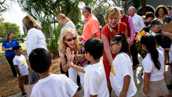 A woman high-fives one of the children from Grace Place during Meet the Kids Day at Grace Place in Naples, Florida on Friday, Jan. 27, 2017. The event gave patrons of the Naples Winter Wine Festival the opportunity to interact with NCEF supported charities and visit with some of the children who have been affected by their donations.