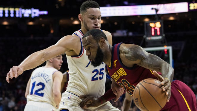 Cleveland Cavaliers' LeBron James, right, drives to the basket against Philadelphia 76ers' Ben Simmons, left, on Friday night. The Sixers won 132-130.