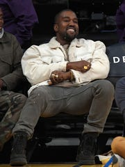 Kanye West watches during the second half of an NBA