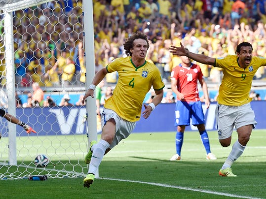Brazil's David Luiz, left, and Fred celebrate after Brazil's opening goal during the World Cup round of 16 soccer match between Brazil and Chile at the Mineirao Stadium in Belo Horizonte, Brazil, Saturday, June 28, 2014. (AP Photo/Martin Meissner)