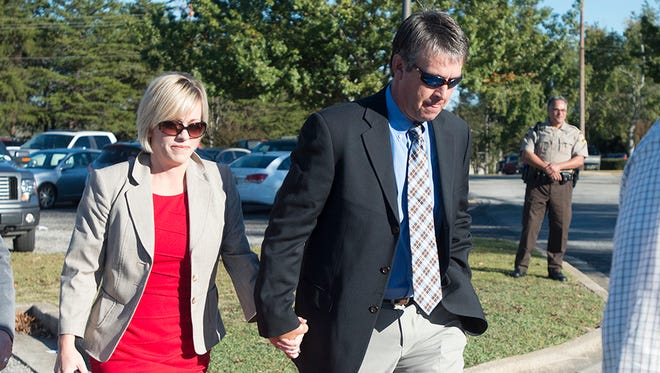 Alabama State Representative Barry Moore, right, walks into the Lee County Justice Center with his wife, Heather Moore, on Thursday, Oct. 30, 2014, in Opelika, Ala. Moore has been charged with lying to a grand jury and committed perjury. A jury is currently deliberating.