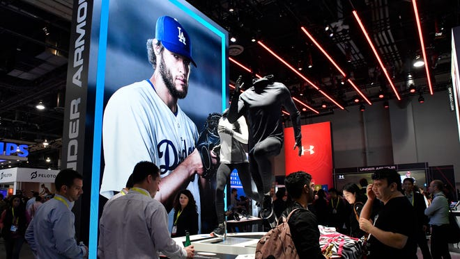 Attendees look over products at the Under Armour booth during CES at the Las Vegas Convention Center.