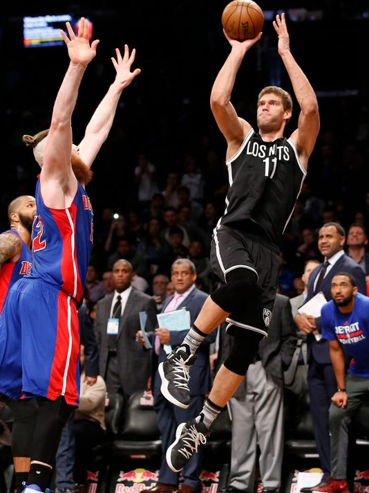 Detroit Pistons center Aron Baynes (12) defends as Brooklyn Nets center Brook Lopez (11) goes up for two points to sink a buzzer-beater that lifted the Nets to victory over the Pistons during the second half of an NBA basketball game, Tuesday, March 21, 2017, in New York. The Nets defeated the Pistons 98-96. (AP Photo/Kathy Willens)