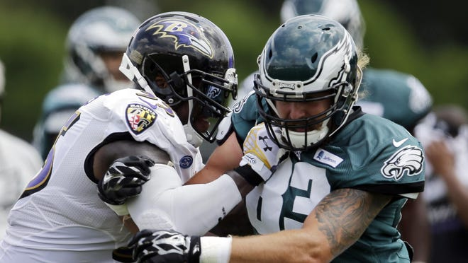 The Ravens' Terrell Suggs (55) and the Eagles' Eric Tomlinson (83) run a drill during a joint practice Wednesday in Philadelphia.