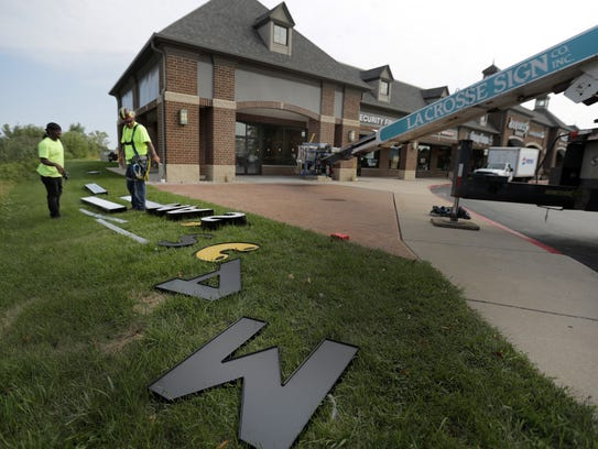 Workers lay out letters for the sign at MACS in Darboy.