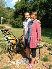 Milford couple Leah and Craig Bennett, shown Thursday June 28, 2018, stand by a butterfly chair installed at the Howell Conference and Nature Center in memory of their late daughter Alexandria. They will be seeking donations to build a treehouse village at the nature center in their daughter's honor.