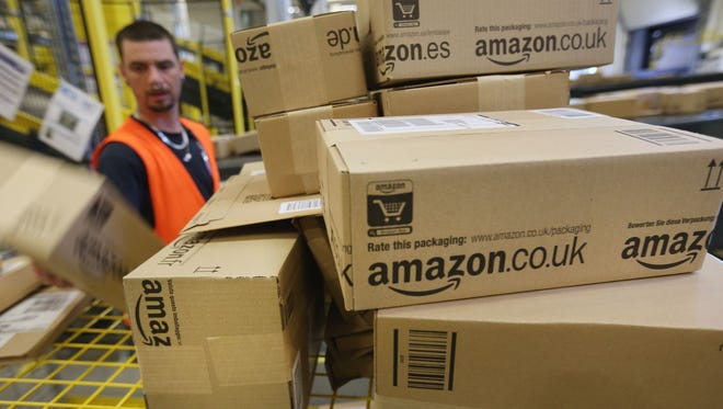 A worker prepares packages for delivery at an Amazon warehouse in Brieselang, Germany.