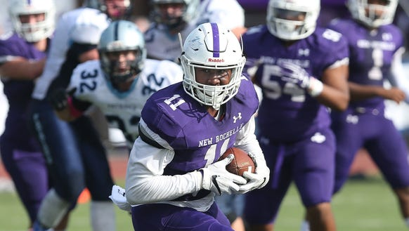 New Rochelle junior Khairi Manns (11) carries the football during his team's 28-14 win over John Jay-East Fishkill in a Section 1 Class AA semifinal at New Rochelle High School Oct. 28, 2017. The Huguenots went on to win their third straight Section 1 title.