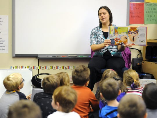 Kristen Starrett, early education literacy specialist with the Muskingum County Public Library, reads to preschoolers during story time at Hopewell Elementary School in Zanesville. The school is one of 98 recognized as Schools of Promise by the Ohio Department of Education.