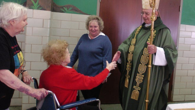Bishop William Friend, right, greets Yvette R. Thompson, seated, and Dorothy Hovious, left, both of Shreveport after services in 2006 at The Cathedral of St. John Berchmans in Shreveport.