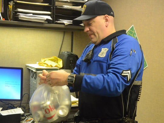 Cpl. Joe Wilder bags some returnable cans for panhandlers.
