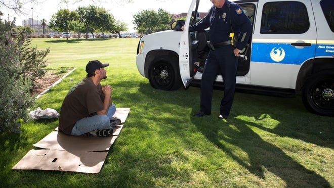 Phoenix Police Department Detective Rusty Stuart talks with Gabriel Shaffer last month in Margaret T. Hance Park. In January, Phoenix adopted a new policy to help connect homeless individuals with quality-of-life services.