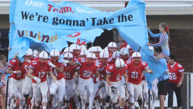 South Salem football players break through the banner before playing Forest Grove on Friday, Sept. 18, 2015.