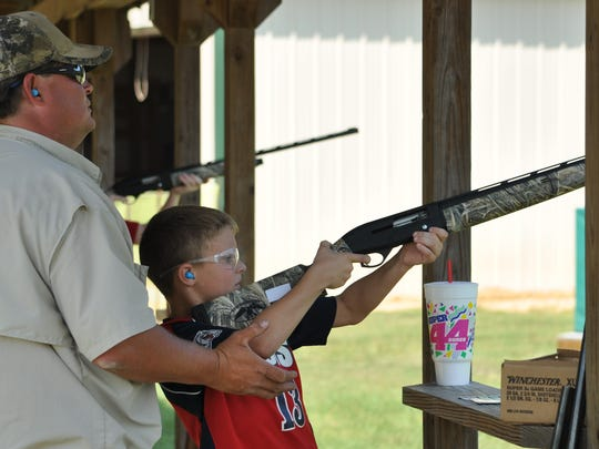 Brayden Sweat prepares to shoot with the help of a volunteer at Central Louisiana's National Hunting and Fishing Day event held in Woodworth.