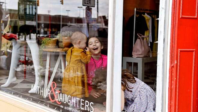 """From left, Hilary Arthur's daughters Reed, 15 months; Violet, 9; and Eleanor, 7, play in Arthur's storefront window on North Beaver Street Friday, March 23, 2018, in York. """"There were definitely moments when I thought, 'Wow, are customers going to judge us for this? Are they going to think this not the most appropriate? Is a kid melting down going to make them uncomfortable?'"""" Arthur said of having her children in the store with her. """"But it really hasn't been that way at all. People have really embraced them."""" A handful of downtown York business owners bring their babies or kids to work, citing daycare costs or the flexibility they enjoy as their own bosses."""