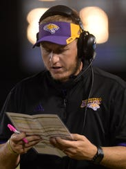 Benton head coach Reynolds Moore checks his play book