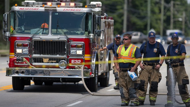 Firefighters hose down the scene of a fatal accident involving a school bus on Westport Rd. July 31, 2017.