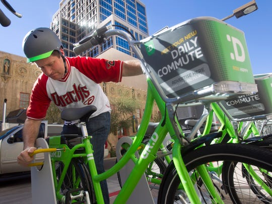 Phoenix Mayor Greg Stanton unlocks a Grid Share Bike before on a four-mile ride from Park Central to CityScape in downtown Phoenix to celebrate Phoenix Bike to Work Day.