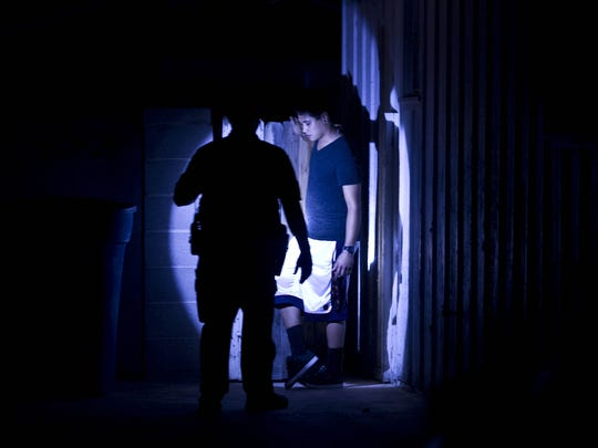 Tempe Officer John Mascarenas shines a light at someone exiting a house during the Safe and Sober operation in Tempe in the early morning of Sept. 1, 2013.