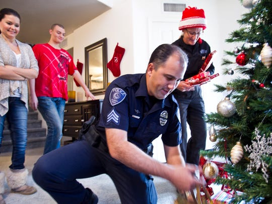 Gilbert Police Sgt. Bill Balafas (center) and officer Mary Jo Kuzmick deliver gifts to Rachel Dupue (left) and her family in 2010.