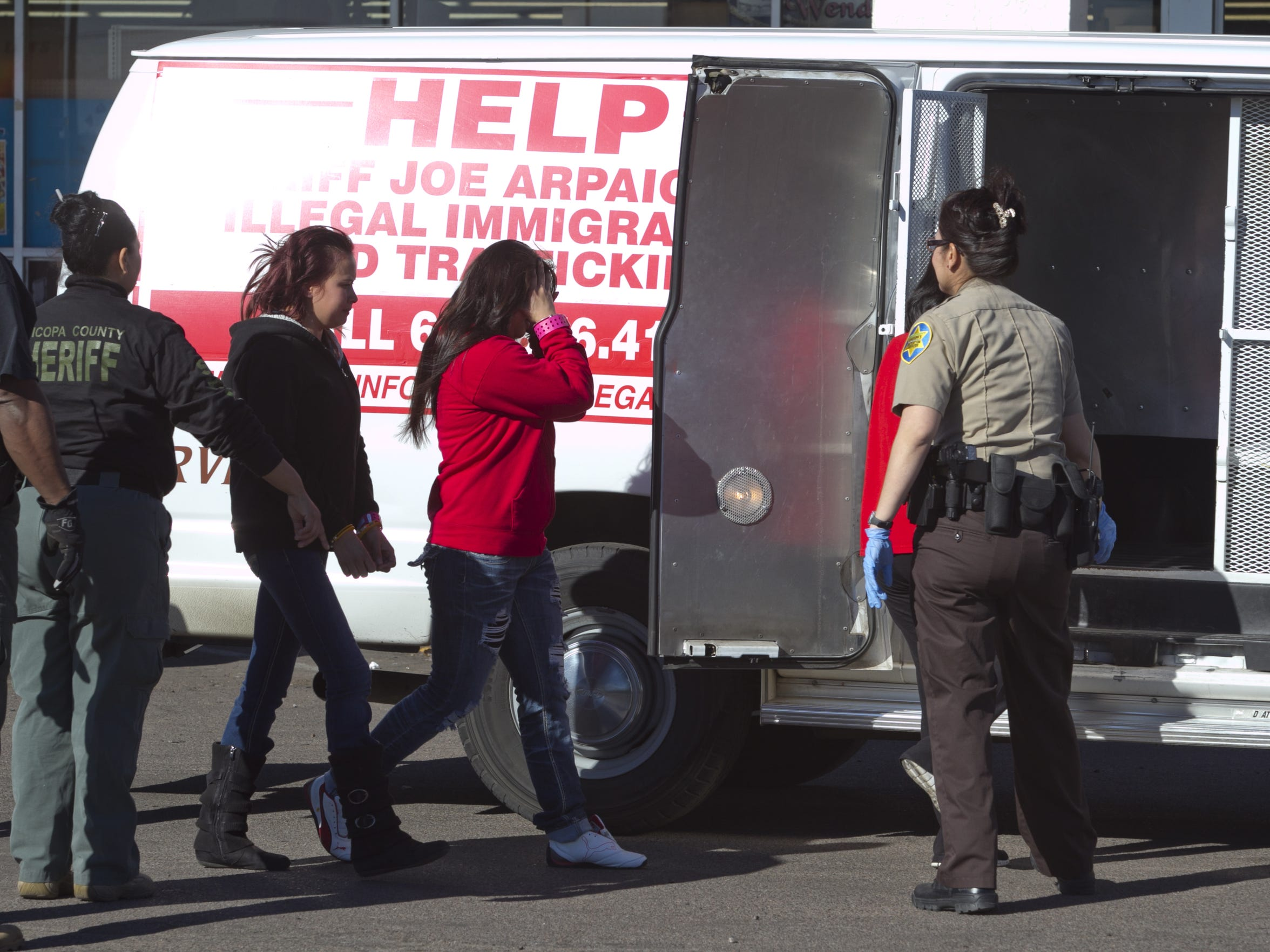 Maricopa County sheriff deputies take into custody several people in 2013 during one of Sheriff Joe Arpaio's many immigration raids.